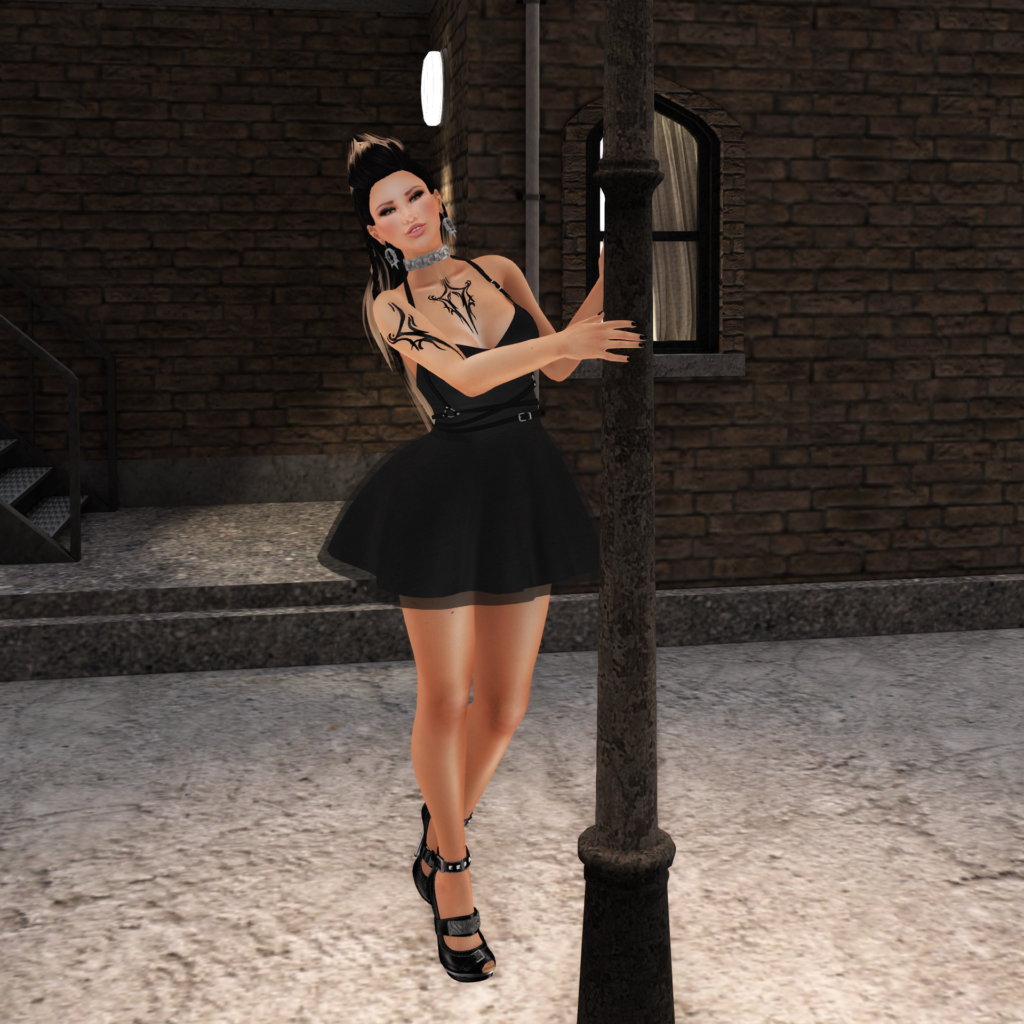 A female Second Life avatar with tattoos dances in a Black dress and smiles at the camera.